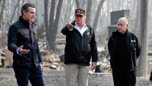 President Donald Trump talks with then Gov.-elect Gavin Newsom (left) and as California Gov. Jerry Brown listens during a visit to a neighborhood impacted by the wildfires in Paradise, California, in November. | AP