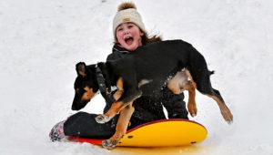 Kylie Silvia, de 7 años, se desliza cuesta abajo sobre una tabla mientras la persigue su perro, Atlas, en la llamada Zona Recreativa Estatal del Norte en el noroeste del estado de Washington. (Scott Terrell/Skagit Valley Herald vía AP)