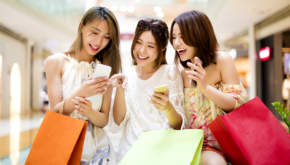 Happy young woman watching smart phone in shopping mall.   Stock Photo