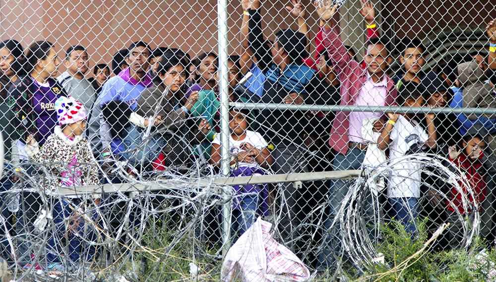 Migrantes centroamericanos esperan comida en El Paso, Texas, el miércoles 27 de marzo de 2019, dentro de una celda erigida por la Oficina de Aduanas y Protección Fronteriza. (AP Foto/Cedar Attanasio)