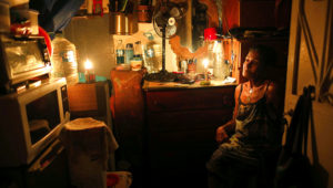 Elizabeth Guzmán Espitia, de 72 años, se sienta en su habitación sin ventanas durante un apagón en el vecindario Santa Cruz del Este, en Caracas, Venezuela, el jueves 14 de marzo de 2019. (AP Foto/Ariana Cubillos)
