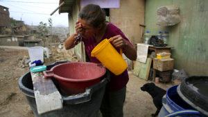 Maria Jimenez lava su cara con agua afuera de su casa en el barrio de Nueva Esperanza en Lima, Perú, el jueves 21 de marzo de 2019. (AP Foto/Martin Mejia)