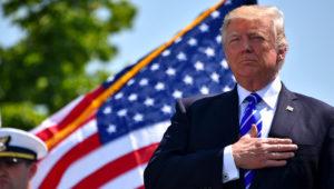 Presidente Donald Trump, con la mano en el pecho delante de una bandera de Estados Unidos.