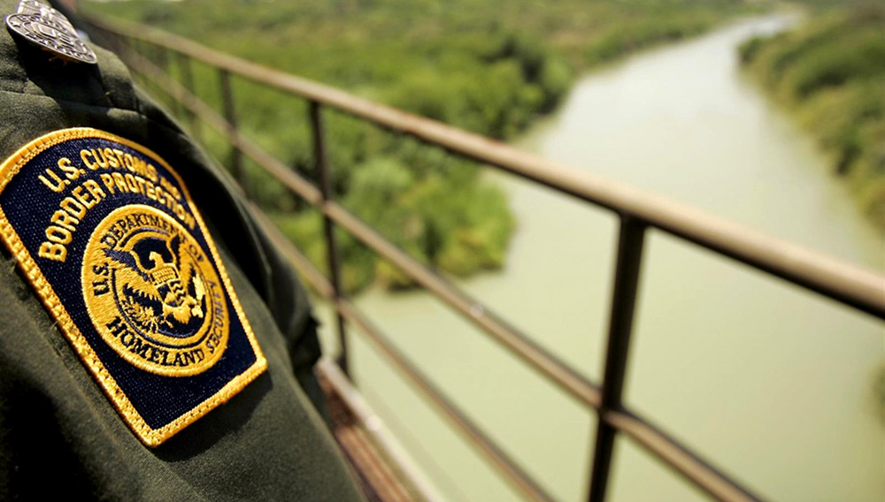 Border Patrol agent Luis Gonzalez looks at the Rio Grande River with Mexico on the left and the U.S. on the right from a railroad bridge in Laredo, Texas May 2, 2006. Hundreds of illegal aliens cross the river each day trying to sneak into the U.S. (Reuters/Rick Wilking)