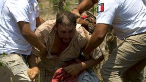 Un migrante centroamericano es detenido por agentes de inmigración mexicanos en la carretera a Pijijiapan, México, el lunes 22 de abril de 2019. (AP Foto/Moisés Castillo)