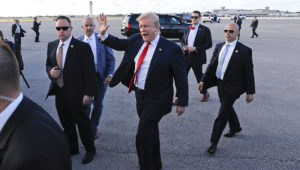 El presidente Donald Trump, rodeado por agentes del Servicio Secreto, saluda a simpatizantes tras llegar al Aeropuerto , Internacional de Palm Beach, el jueves 18 de abril del 2019, en West Palm Beach, Florida. (AP Foto/Pablo Martínez Monsivais)