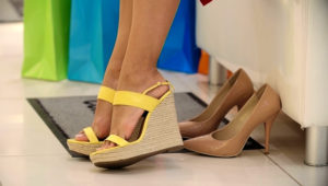 Beautiful blonde girl trying on wedge heels in shoe store. Stock Video Footage - Storyblocks Video