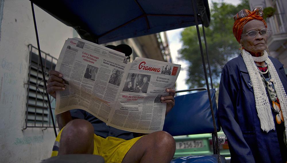 ARCHIVO - En esta fotografía de archivo del 3 de febrero de 2015, un hombre lee una copia del diario Granma, órgano del oficial Partido Comunista, mientras una mujer pasa a su lado en La Habana. (AP Foto/Ramon Espinosa, Archivo)