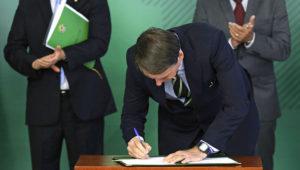 En esta imagen de archivo, tomada el 15 de enero de 2019, el presidente de Brasil, Jair Bolsonaro, firma un decreto para aliviar las restricciones sobre la propiedad de armas, en el palacio presidencial Planalto, en Brasilia, Brasil. (AP Foto/Eraldo Peres, archivo)