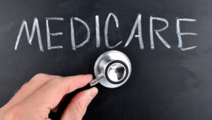"""Blackboard on which """"medicare"""" is written, with a hand putting a stethoscope to. Image source: Getty Images."""