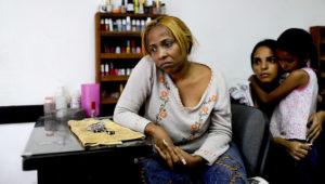 La manicurista María Trinidad Tobar espera clientes en un salón de belleza en Caracas, Venezuela, el martes 19 de marzo de 2019. (AP Foto / Natacha Pisarenko)