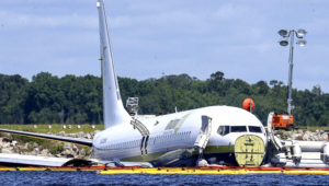 A charter plane carrying 143 people and traveling from Cuba to north Florida sits in a river at the end of a runway. (Gary McCullough / AP)