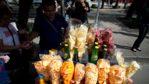 FILE - In this July 5, 2016 file photo, a street vendor sells fried snacks packaged in plastic bags in Mexico City. Mexico City lawmakers announced on Thursday, May 9, 2019 they have passed a ban on plastic bags, utensils and other disposable plastic items to take effect at the end of 2020, giving businesses more than a year to make the switch to biodegradable products. (AP Photo/Eduardo Verdugo, File)