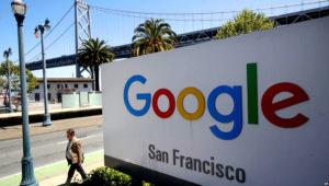 A man walks past a Google sign outside with a span of the Bay Bridge at rear in San Francisco, May 1, 2019. | AP