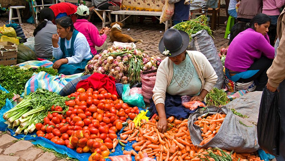 Women sitting on ground with produce at Sunday Market.