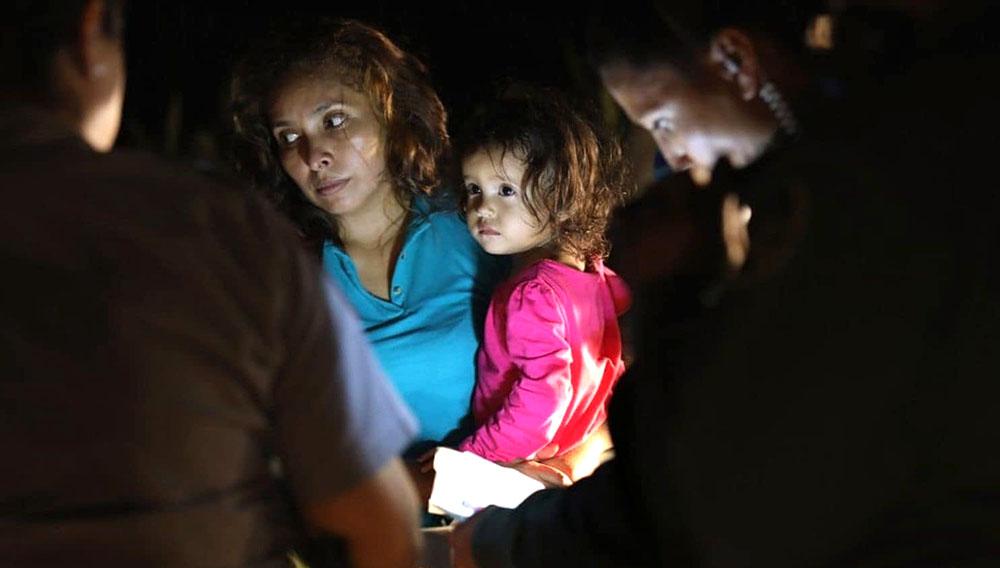 Una niña hondureña y su madre son llevadas bajo custodia. (Crédito: John Moore/Getty Images)
