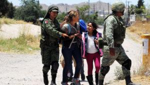 Miembros de la Guardia Nacional mexicana detienen a una madre y su hija cuando tratan de cruzar la frontera hacia Estados Unidos, el 21 de junio de 2019 en Ciudad Juárez.
