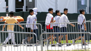 Migrant children are escorted through the Homestead Temporary Shelter for Unaccompanied Children on Good Friday, April 19, 2019. Photo: MATIAS J. OCNER / MIAMI HERALD