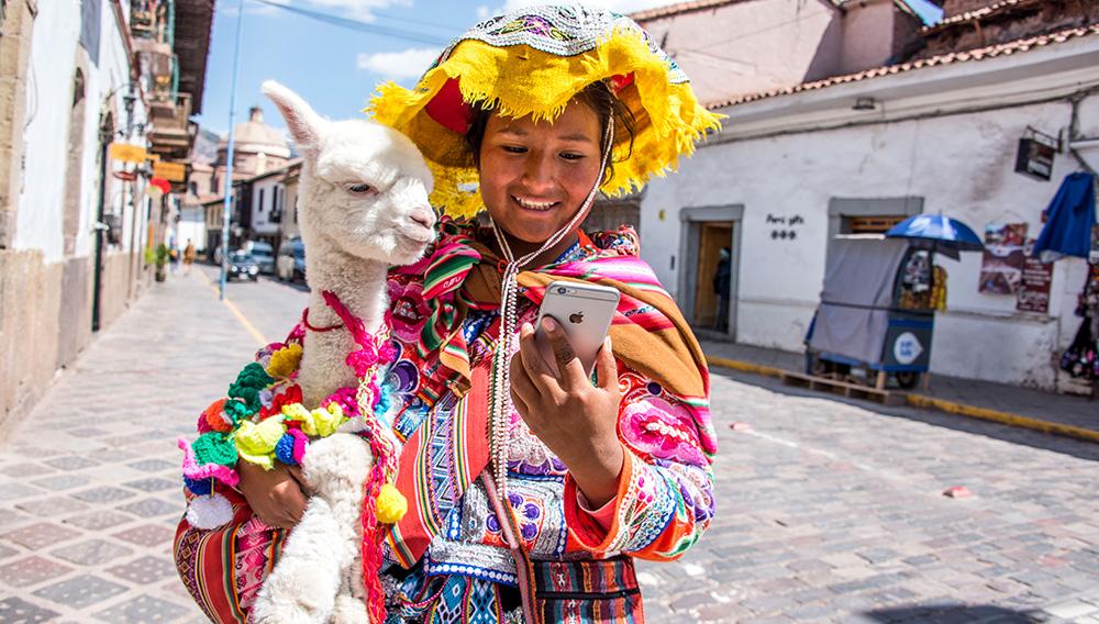 Niña vestida con la indumentaria típica del valle del Colca abraza a una alpaca mientras mira su teléfono móvil en una calle de la ciudad de Arequipa, en el sur de Perú.   Foto: Ministerio de Transportes y Comunicaciones de Perú.