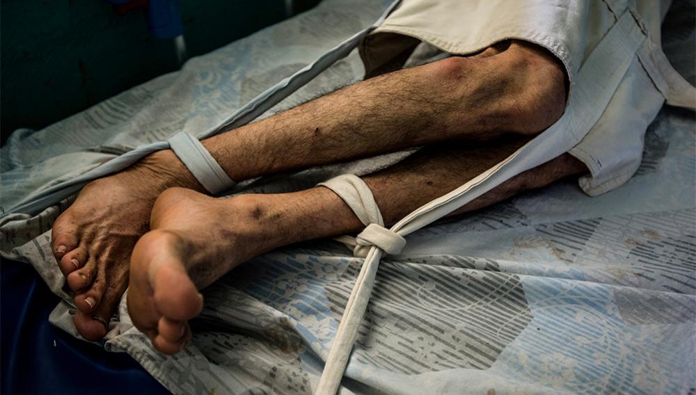 Raúl Martínez, un paciente esquizofrénico que no tiene la dosis necesaria de sus medicamentos, estaba amarrado en su cama del Hospital Psiquiátrico El Pampero, en Barquisimeto, para evitar que se hiciera daño. Credit Meridith Kohut para The New York Times