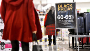 """Shoppers walk past a placard that states """"Black Friday preview"""" at a Macy's store as pre-Thanksgiving and Christmas holiday shopping accelerates at the King of Prussia Mall in King of Prussia, Pennsylvania, U.S. November 22, 2019. REUTERS/Mark Makela"""