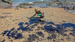 Un activista limpia las manchas de crudo en el mar brasileño. Fuente: ANTONELLO VENERI / AFP