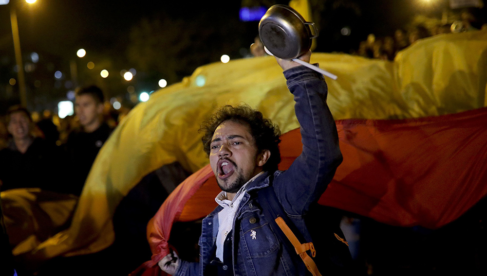 An anti-government protester waves a pot in Bogota, Colombia, Saturday, Nov. 23, 2019. Authorities in Colombia are maintaining a heightened police and military presence in the nation's capital following two days of unrest. (AP Photo/Ivan Valencia)