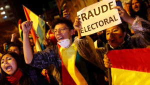 """A protestor holds a banner reading """"Electoral Fraud"""" as she takes part in a march in La Paz, Bolivia, Oct. 25, 2019. Photo: Reuters"""