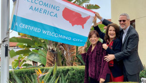Chula Vista Mayor Mary Casillas Salas (left), Councilmember Jill Galvez and City Attorney Glen Googins outside city hall with the welcoming flag. Photo: Times of San Diego.