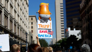 A group of people protesting a visit by President Donald Trump wait for his arrival to a fundraiser Wednesday, Sept. 18, 2019, in San Diego. Trump was scheduled to attend a fundraiser and visit the border before leaving later Wednesday. (AP Photo/Gregory Bull)