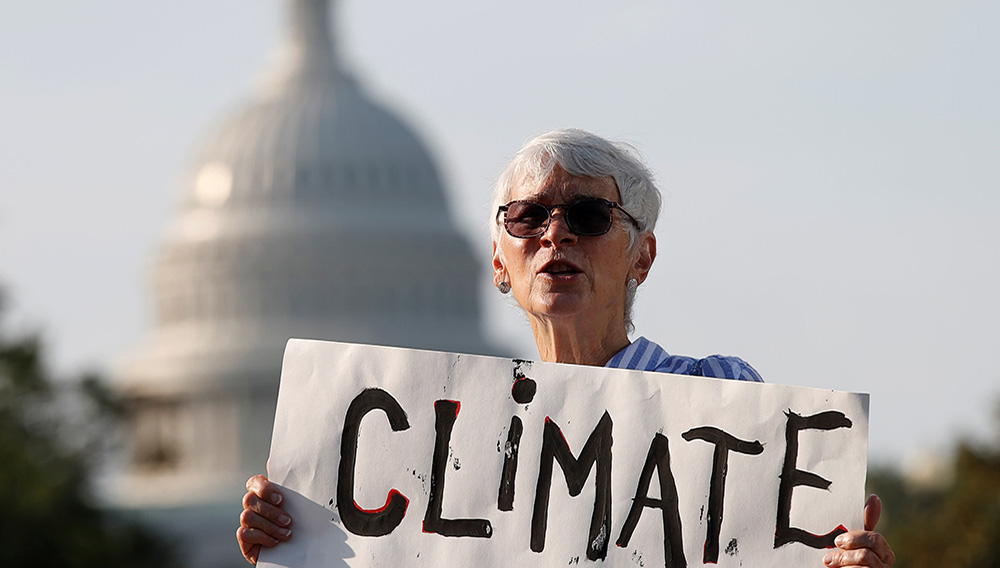 An environmental activist holds up a sign in Washington D.C. Former California governor Jerry Brown said the U.S. state will work with China to tackle climate change issues. © Reuters