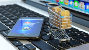Online shopping, internet purchases and e-commerce concept, modern mobile phone with buy button on the screen and shopping cart full of package boxes on computer laptop keyboard. Shutterstock