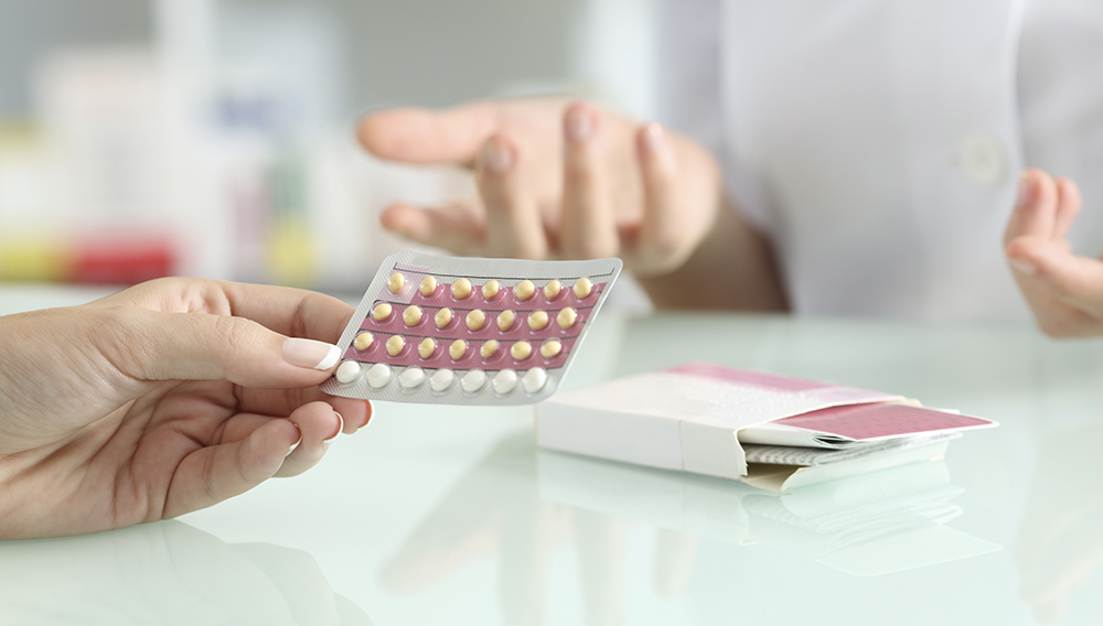 Close up of a girl hands buying contraceptive pills and pharmacist explaining in a pharmacy. Photo: Antonio Guillem