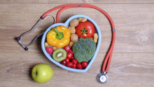 Heart shaped dish with vegetables and stethoscope isolated on wooden background. Photo: Adobe stock