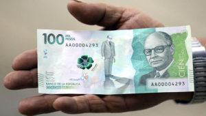 Un hombre muestra el nuevo billete colombiano de 100.000 pesos en Bogotá, Colombia, jueves 31 de marzo de 2016. El billete, el de mayor denominación en el país, entró en circulación el 31 de marzo Equivale a unos 33 dólares. (AP Foto/Fernando Vergara)