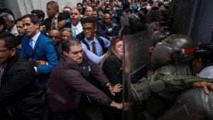 Diputados forcejean con la Guardia Nacional. A Juan Guaidó (vestido azul), presidente encargado, se le impidió entrar a la sede de la Cámara, donde debía ser reelegido como su líder. Foto: Efe