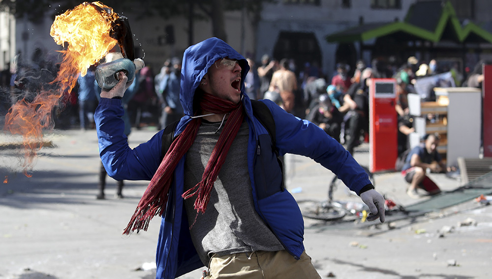 """An anti-government protester throws a firebomb at police amid a march by students and union members in Santiago, Chile, Monday, Oct. 21, 2019. Protesters defied an emergency decree and confronted police in Chile's capital on Monday, continuing disturbances that have left at least 11 dead and led the president to say the country is """"at war."""" (AP Photo/Miguel Arenas)"""