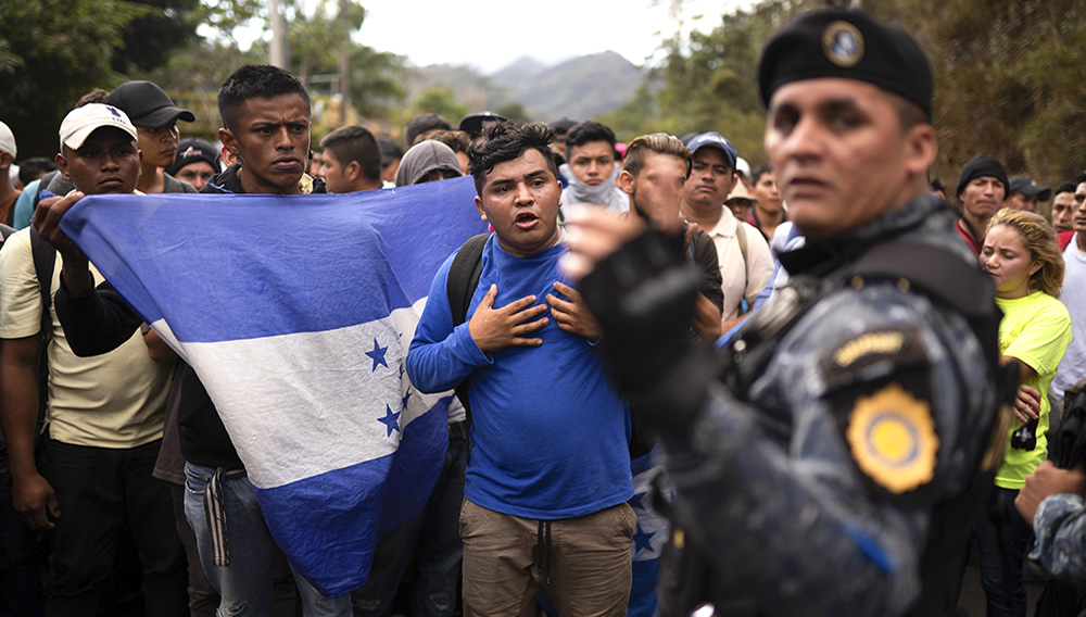 """Honduran migrants walking in a group stop before Guatemalan police near Agua Caliente, Guatemala, Thursday, Jan. 16, 2020, on the border with Honduras. Less-organized migrants, tighter immigration control by Guatemalan authorities and the presence of U.S. advisers have reduced the likelihood that the hundreds of migrants who departed Honduras will form anything like the cohesive procession the term """"caravan"""" now conjures. (AP Photo/Santiago Billy)"""