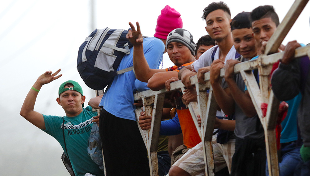 Migrants ride on top of a truck moving along the highway, in hopes of reaching the distant United States, from San Pedro Sula, Honduras, early Wednesday, Jan. 15, 2020. Hundreds of Honduran migrants started walking and hitching rides Wednesday from the city of San Pedro Sula, in a bid to form the kind of migrant caravan that reached the U.S. border in 2018. (AP Photo/Delmer Martinez)