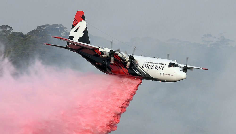 A C-130 Hercules drops water over bushfires in New South Wales. Credit: AFP