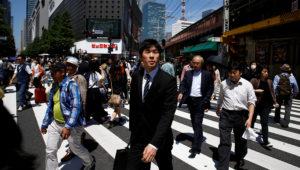 Varias personas cruzan una calle en el barrio de negocios de Tokio. REUTERS/Thomas Peter