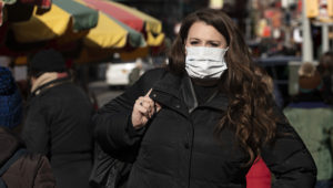 """The U.S. safety advisory for China now stands at """"Level 4: Do Not Travel,"""" after the WHO declared the Wuhan coronavirus a global health emergency. Here, a woman wears a mask in New York out of concern for the deadly respiratory virus. CREDIT MARK LENNIHAN / AP"""