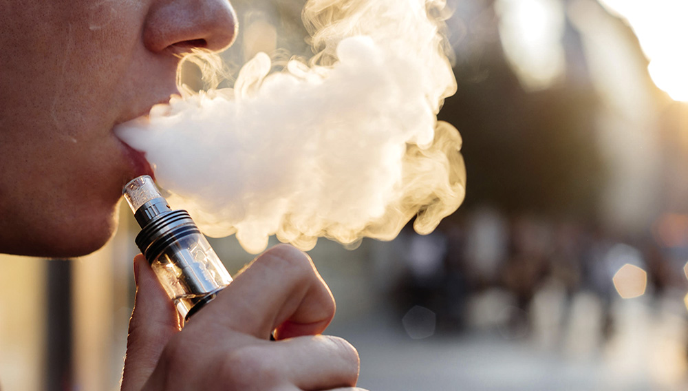 Man using vape or electronic cigarette against the background of the city.   Photo: ©fedorovacz - stock.adobe.com