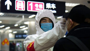 A health worker checks the temperature of a man entering the Beijing subway on Jan. 26. The decrease in travelers has raised concerns about the impact of the new conronavirus on the global economy. Photo: Getty Images