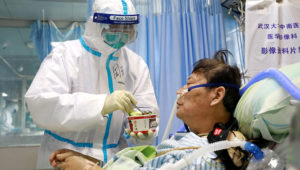 A nurse in a protective suit feeds a coronavirus patient inside an isolated ward at Zhongnan Hospital of Wuhan University on February 8, 2020.   China Daily via Reuters