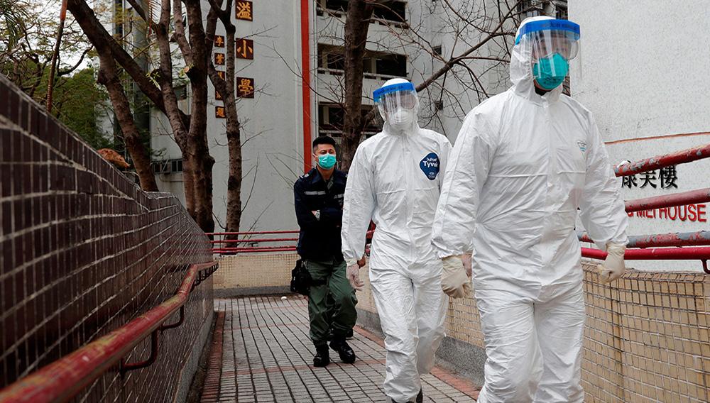 Los trabajadores de la salud caminan mientras evacuan a los residentes de un edificio de viviendas públicas, luego del brote del nuevo coronavirus, afuera de la Casa Hong Mei, en la propiedad Cheung Hong en Hong Kong, China, 11 de febrero de 2020. (REUTERS/Tyrone Siu)