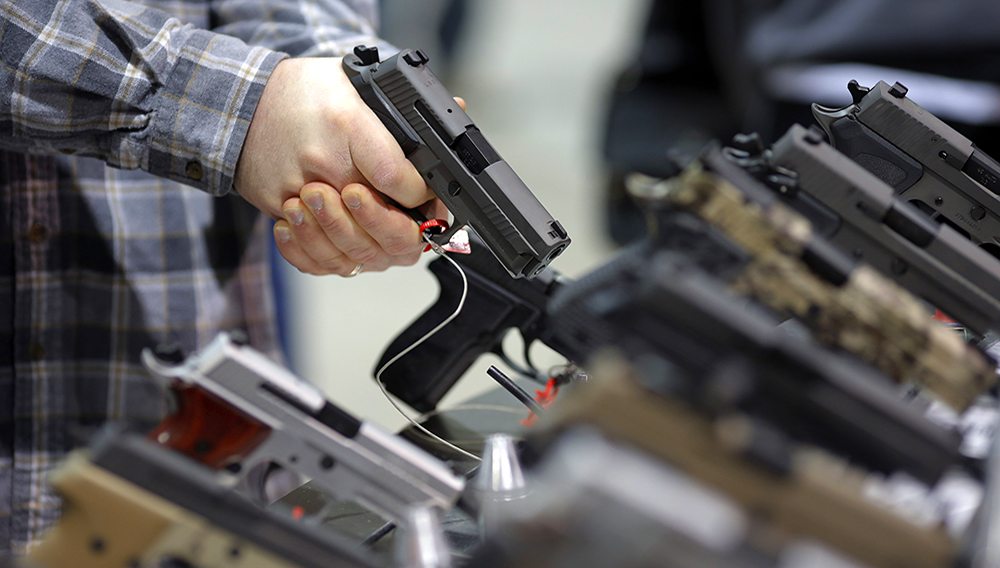A visitor holds a pistol at a gun display during a National Rifle Association outdoor sports trade show on February 10, 2017 in Harrisburg, Pennsylvania. (Photo credit should read DOMINICK REUTER/AFP/Getty Images)