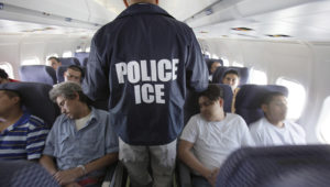 In this May 25, 2010, file photo, an Immigration and Customs Enforcement agent walks down the aisle among shackled Mexican immigrants aboard a U.S. Immigration and Customs Enforcement charter jet for deportation, flying between Chicago, Il., and Harlingen, Texas. Associated Press/Photo by: LM Otero