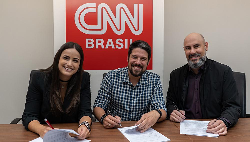 Mari Palma e Phelipe Siani posam para foto na assinatura do contrato, ao lado de Douglas Tavolaro, CEO e cofundador da CNN Brasil/Divulgação