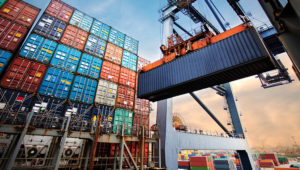 Container loading in a Cargo freight ship with industrial crane. Container ship in import and export business logistic company. | Molpix/Shutterstock